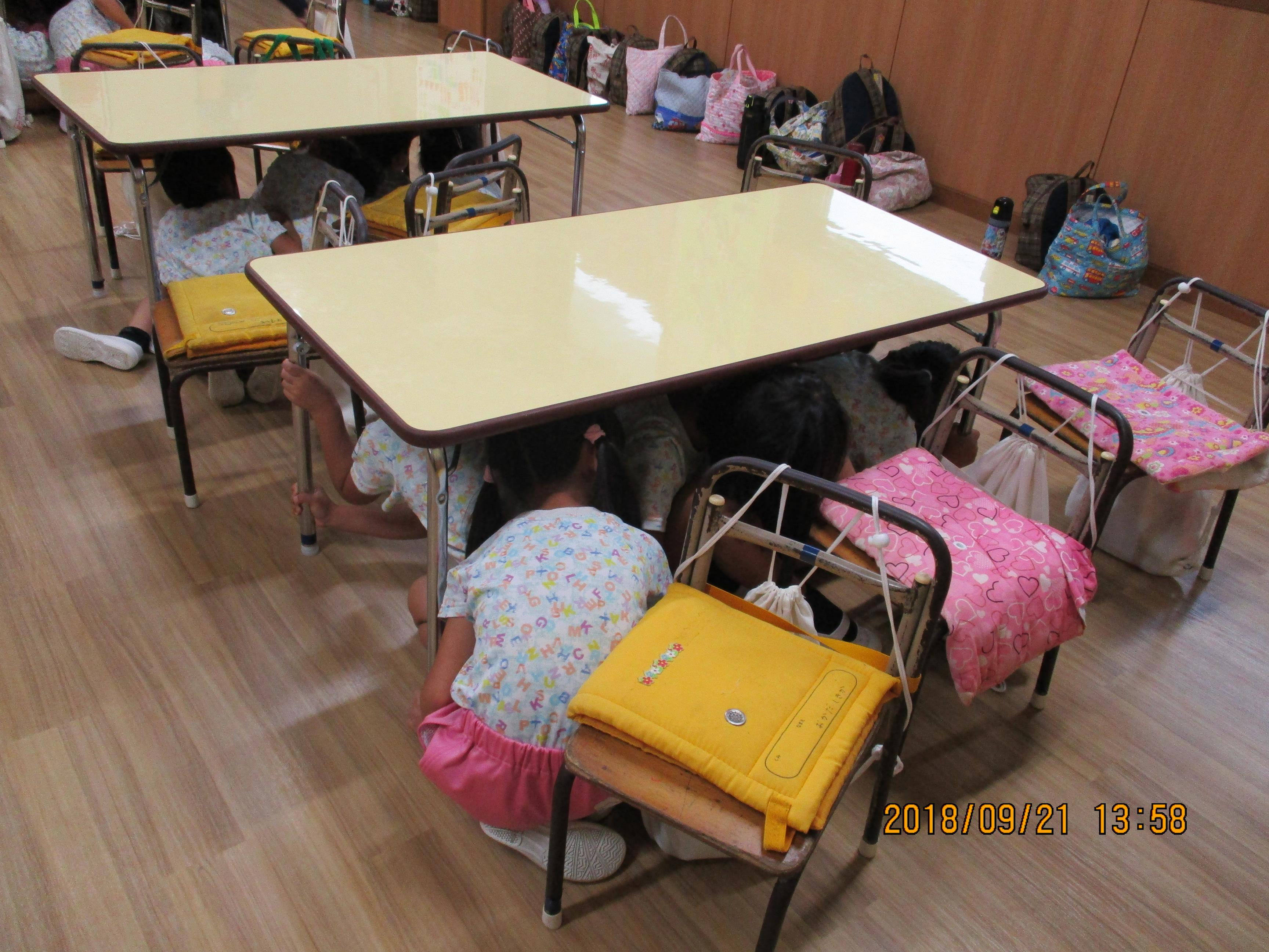 地震発生のアナウンスで一斉に机の下へ