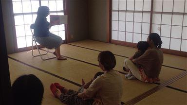 和室の畳の上で読み手が椅子に座り、その前に親子で読み聞かせを楽しんでいる画像